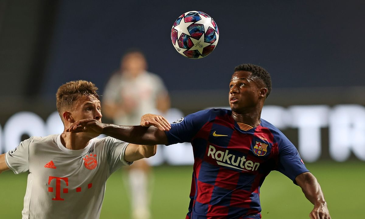 Barcelona's Ansu Fati, right, is challenged by Bayern's Joshua Kimmich during the Champions League quarterfinal soccer match between Barcelona and Bayern Munich in Lisbon, Portugal, Friday, Aug. 14, 2020. Barcelona's Ansu Fati has been called up to Spain's national team for the first time.