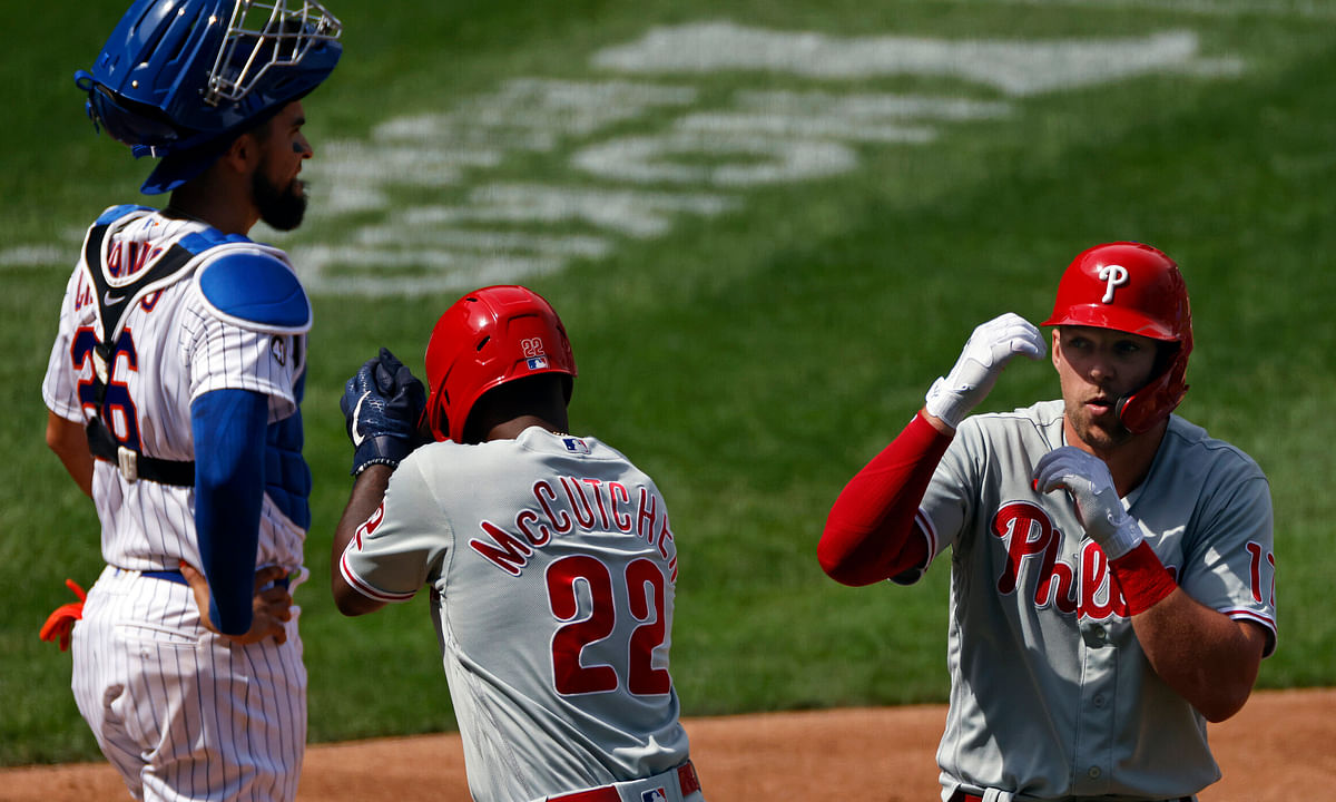 Rhys Hoskins celebrates a two-run home run with Andrew McCutchen (22) in front of Mets catcher Robinson Chirinos Monday