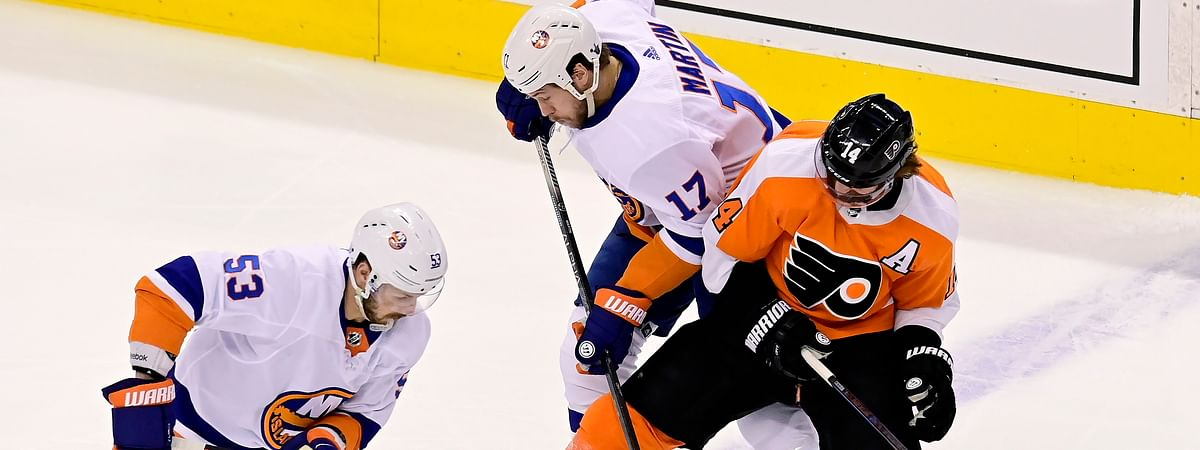 Philadelphia Flyers center Sean Couturier (14) tries to hold onto the puck under pressure from New York Islanders center Casey Cizikas (53) and teammate Matt Martin (17) during the second period of an NHL Stanley Cup Eastern Conference playoff hockey game in Toronto, Ontario, Tuesday, Sept. 1, 2020.