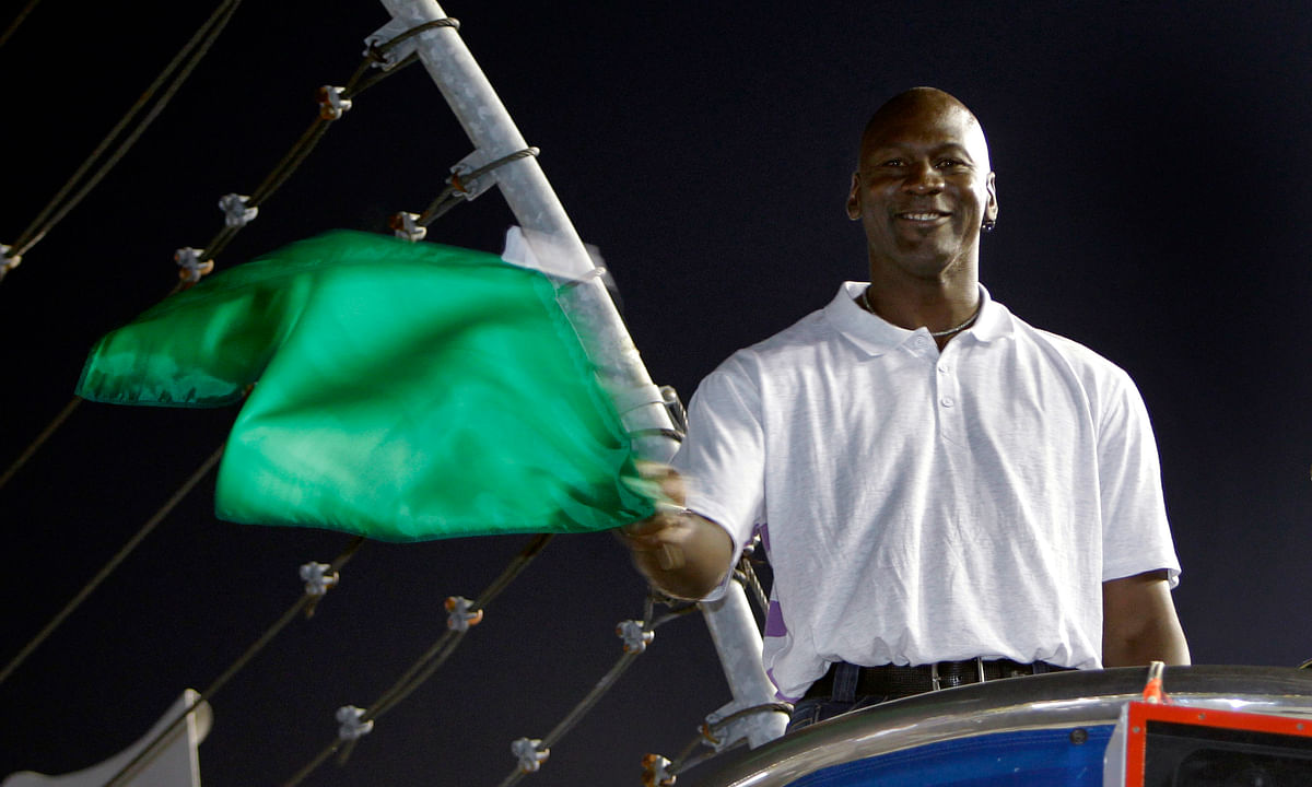 In this May 22, 2010, file photo, Charlotte Bobcats owner Michael Jordan practices waving the green flag before a NASCAR All-Star auto race at Charlotte Motor Speedway in Concord, N.C. Denny Hamlin is starting his own race car team in partnership Jordan and Bubba Wallace as the driver.