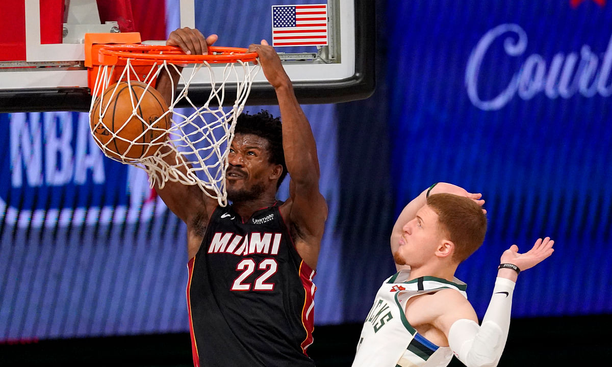 Miami Heat's Jimmy Butler (22) dunks the ball after getting past Milwaukee Bucks' Donte DiVincenzo.