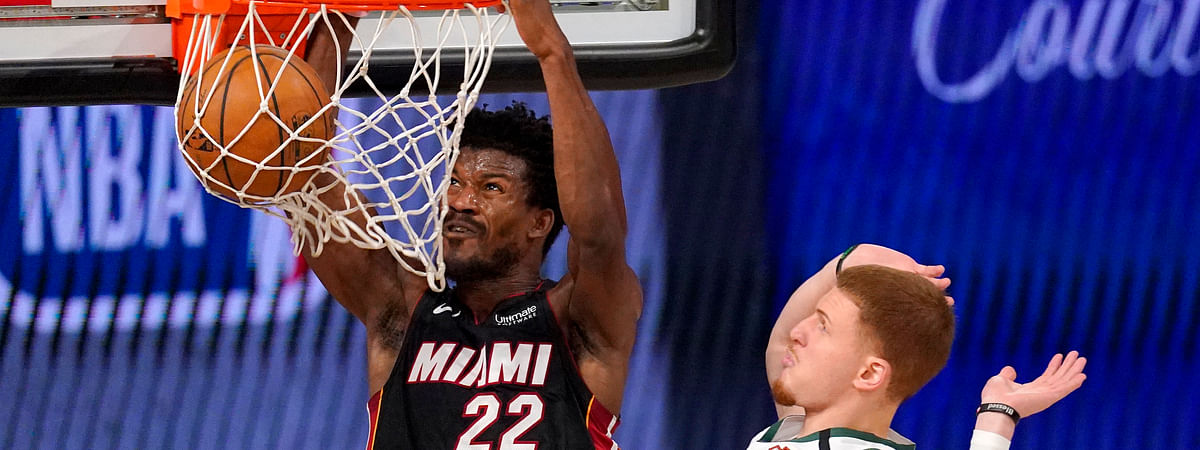 Miami Heat's Jimmy Butler (22) dunks the ball after getting past Milwaukee Bucks' Donte DiVincenzo (0) during the second half of an NBA basketball conference semifinal playoff game, Monday, Aug. 31, 2020, in Lake Buena Vista, Fla.