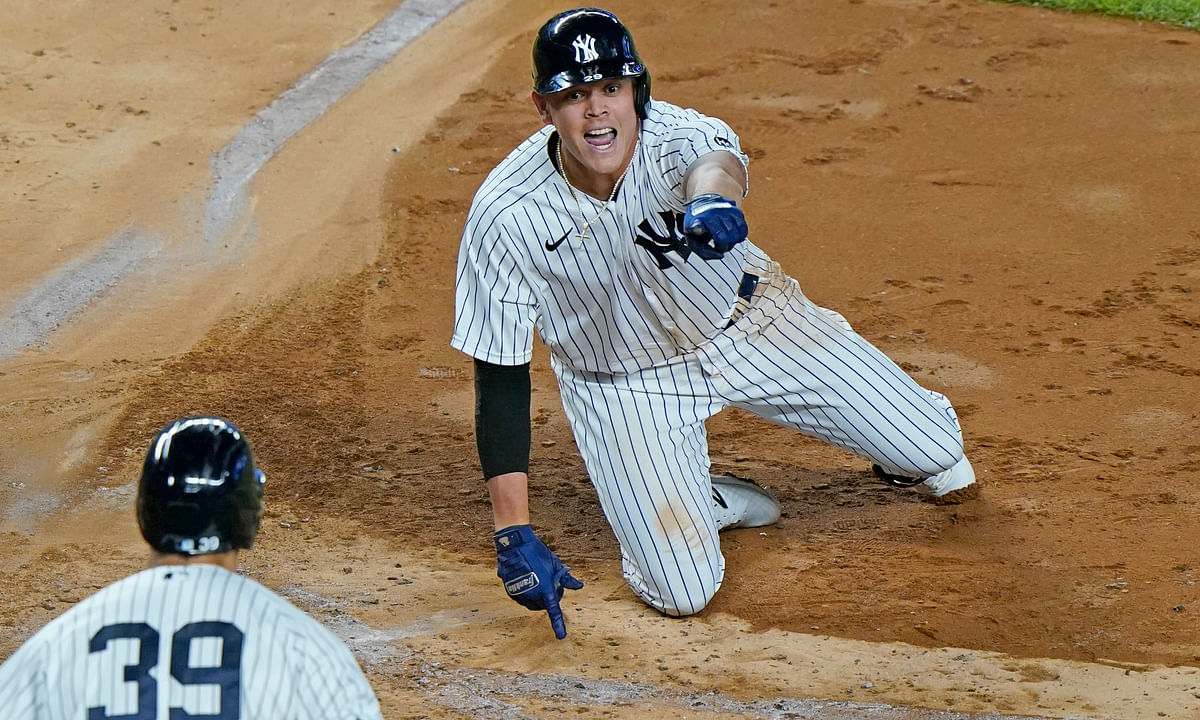 New York Yankees Gio Urshela, right, says he was safe after scoring during the sixth in of the team's baseball game against the Tampa Bay Rays, Tuesday, Sept. 1, 2020, at Yankee Stadium in New York. Urshela hit a two-run double, then scored on an error. Yankees' Mike Tauchman (39) watches.