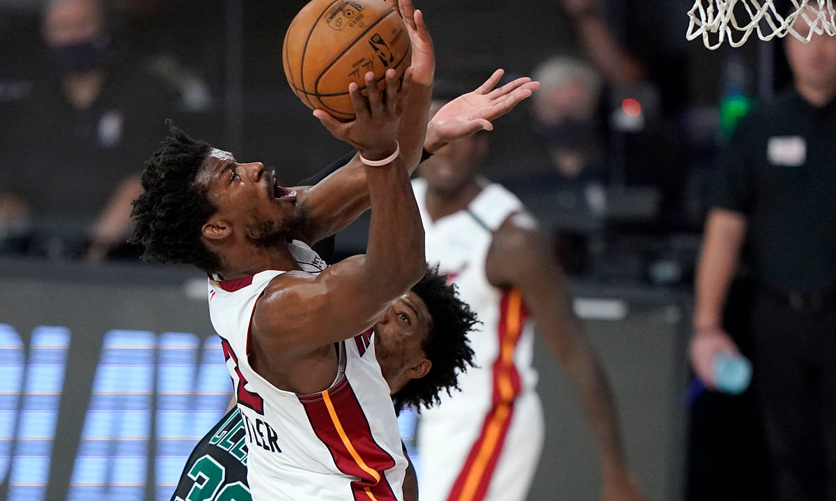 Miami Heat's Jimmy Butler, front, goes up for a shot over Boston Celtics' Marcus Smart, rear, during the first half of an NBA conference final playoff basketball game, Tuesday, Sept. 15, 2020, in Lake Buena Vista, Fla.