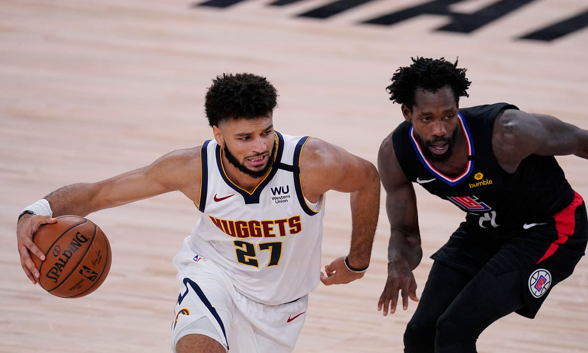 Denver Nuggets guard Jamal Murray (27) drives around LA Clippers guard Patrick Beverley. Beverley is out tonight.