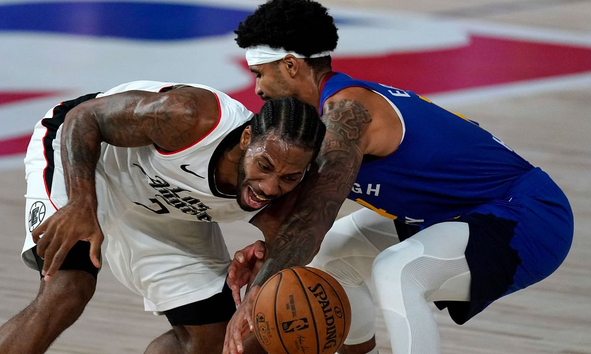Los Angeles Clippers' Kawhi Leonard, left, is fouled by Denver Nuggets' Gary Harris during the second half of an NBA conference semifinal playoff basketball game, Friday, Sept. 11, 2020, in Lake Buena Vista, Fla.