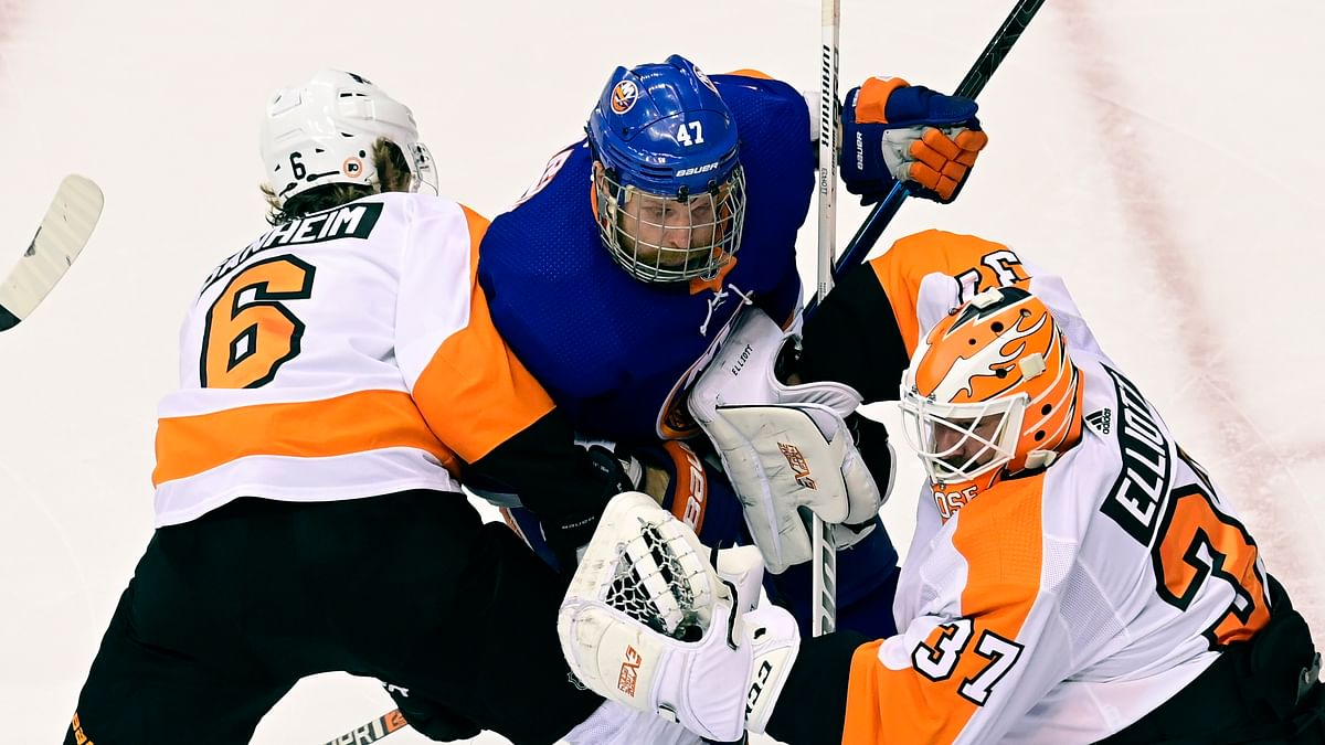 New York Islanders center Leo Komarov (47) and Philadelphia Flyers defenseman Travis Sanheim (6) battle for position in front of Flyers goaltender Brian Elliott (37) during the second period of an NHL Stanley Cup Eastern Conference playoff hockey game, Sunday, Aug. 30, 2020 in Toronto.