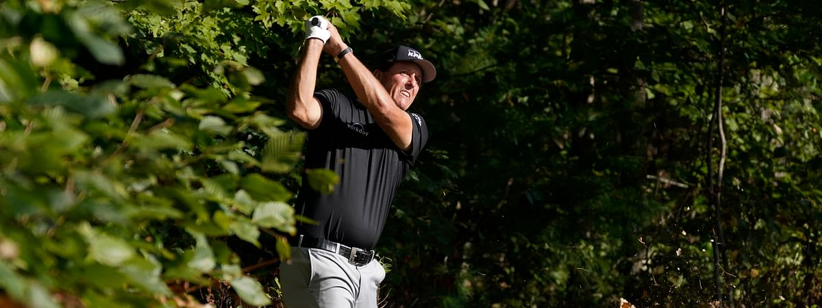 Phil Mickelson watches his shot out of the woods and onto the 14th green during the second round of the Northern Trust golf tournament at TPC Boston, Friday, Aug. 21, 2020, in Norton, Mass.