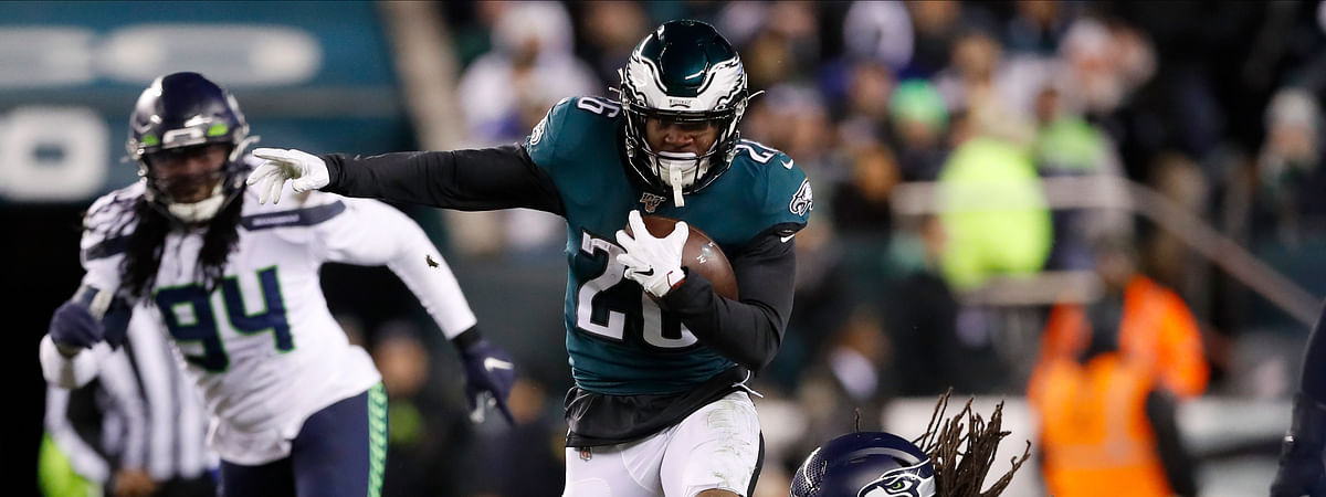 In this Sunday, Jan. 5, 2020 file photo, Philadelphia Eagles' Miles Sanders (26) tries to run past Seattle Seahawks' Jadeveon Clowney (90) during the first half of an NFL wild-card playoff football game against the Seattle Seahawks in Philadelphia. Miles Sanders shared running duties with Jordan Howard last season and still led all rookies in scrimmage yards, setting a Philadelphia Eagles franchise record in the category.