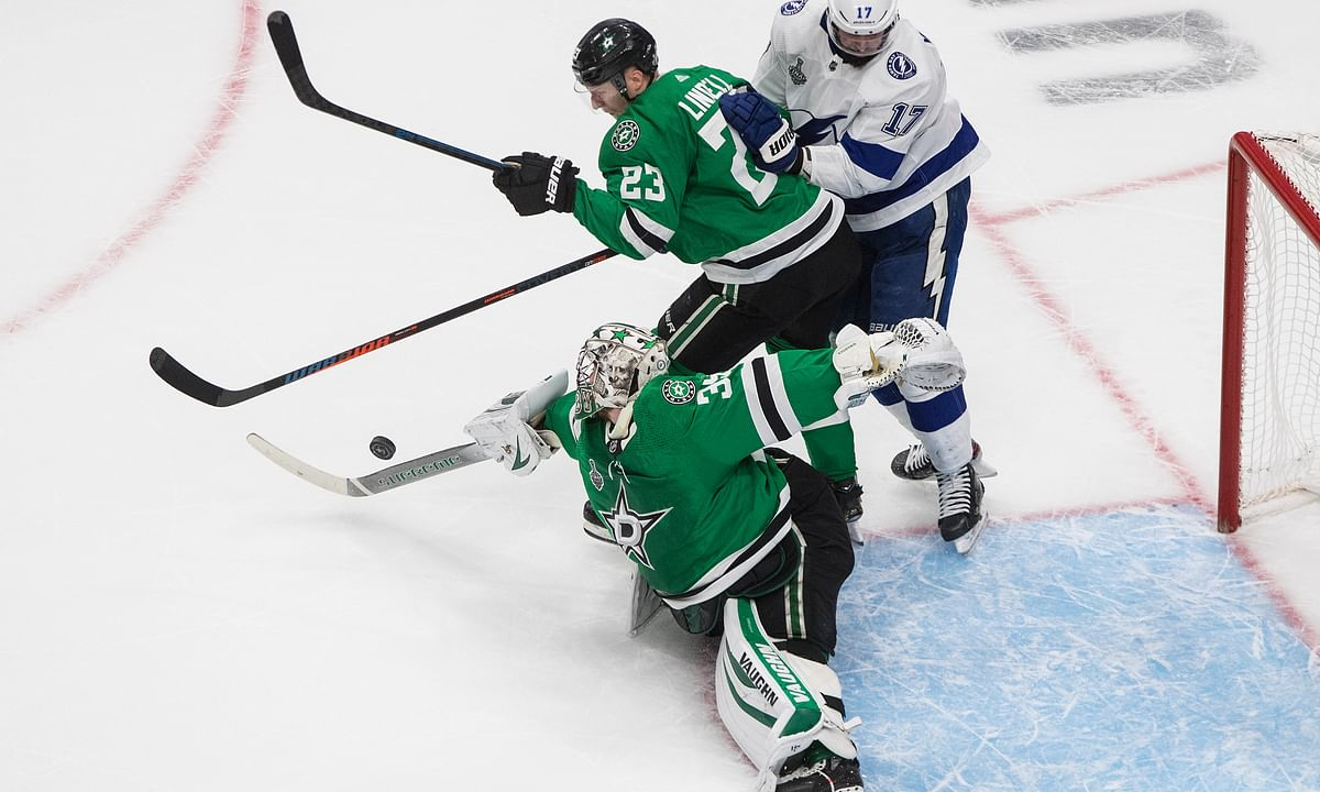 Dallas Stars goaltender Anton Khudobin (35) turns the puck away as Tampa Bay Lightning center Alex Killorn (17) and Stars defenseman Esa Lindell (23) look for the puck during the second period of Game 3 of the NHL hockey Stanley Cup Final, Wednesday, Sept. 23, 2020, in Edmonton, Alberta.