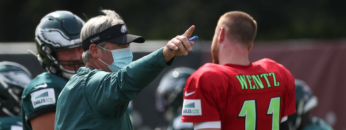 Philadelphia Eagles head coach Doug Pederson, left, gives instructions to quarterback Carson Wentz (11) during an NFL football training camp practice in Philadelphia, Friday, Aug. 21, 2020.