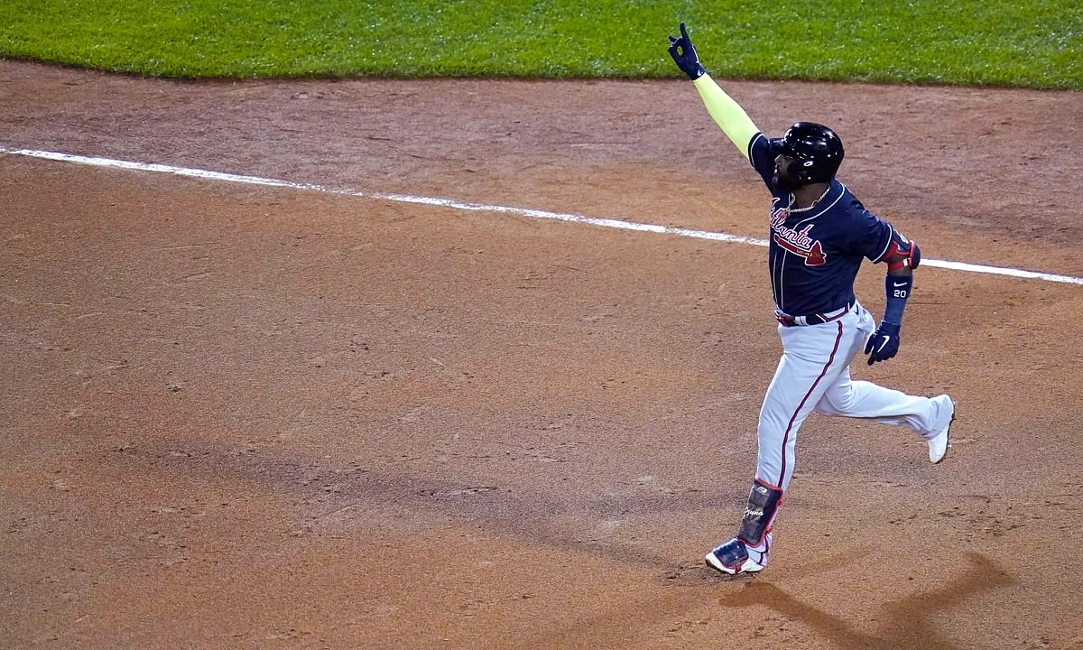 Atlanta Braves designated hitter Marcell Ozuna raises his arm as he rounds the bases on his solo home run in the seventh inning of a baseball game against the Boston Red Sox, Wednesday Sept. 2, 2020, in Boston.