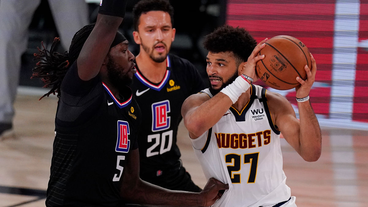Denver Nuggets' Jamal Murray (27) drives around Los Angeles Clippers' Montrezl Harrell (5) and Landry Shamet (20) during the second half of an NBA conference semifinal playoff basketball game Saturday, Sept. 5, 2020, in Lake Buena Vista, Fla.