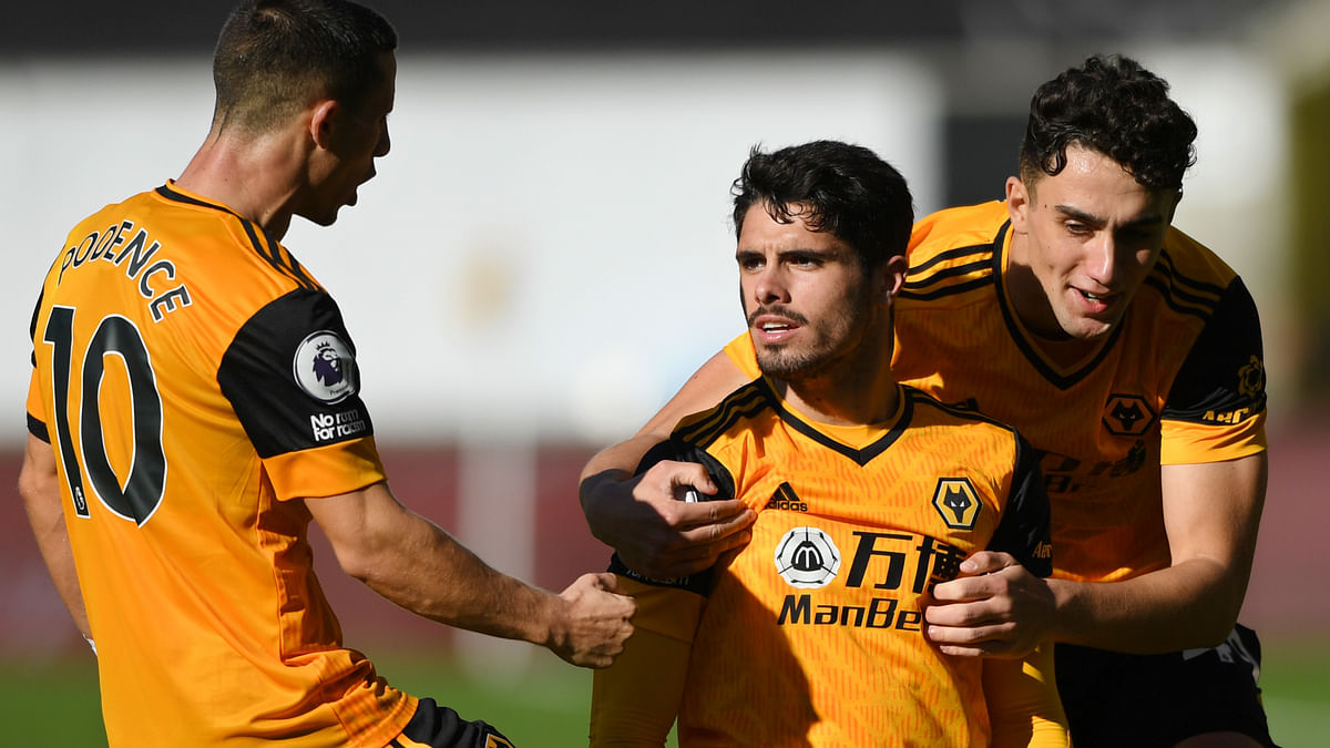 Wolverhampton Wanderers' Pedro Neto, centre celebrates with team mates after scoring his side's opening goal during an English Premier League soccer match between Wolverhampton Wanderers and Fulham at the Molineux Stadium in Wolverhampton, England, Sunday Oct. 4, 2020.