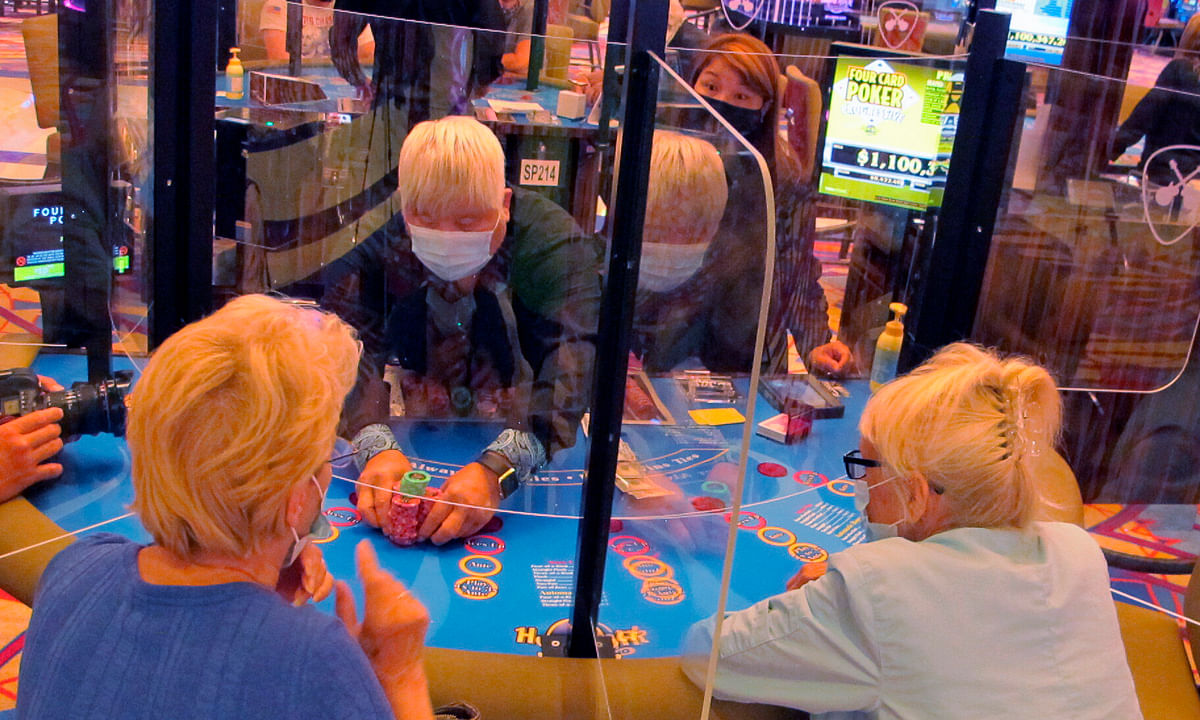See-through barriers separate gamblers and a dealer at a card table at the Hard Rock casino in Atlantic City, N.J., on July 2, 2020, the first day it reopened after being closed for four months due to the coronavirus outbreak.