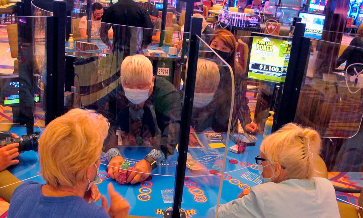 See-through barriers separate gamblers and a dealer at a card table at the Hard Rock casino in Atlantic City, N.J., on July 2, 2020, the first day it reopened after being closed for four months due to the coronavirus outbreak. American Gaming Association President Bill Miller said Tuesday, Oct. 27, 2020, the industry is adapting to the pandemic but needs assistance from the government for its casinos and workers.