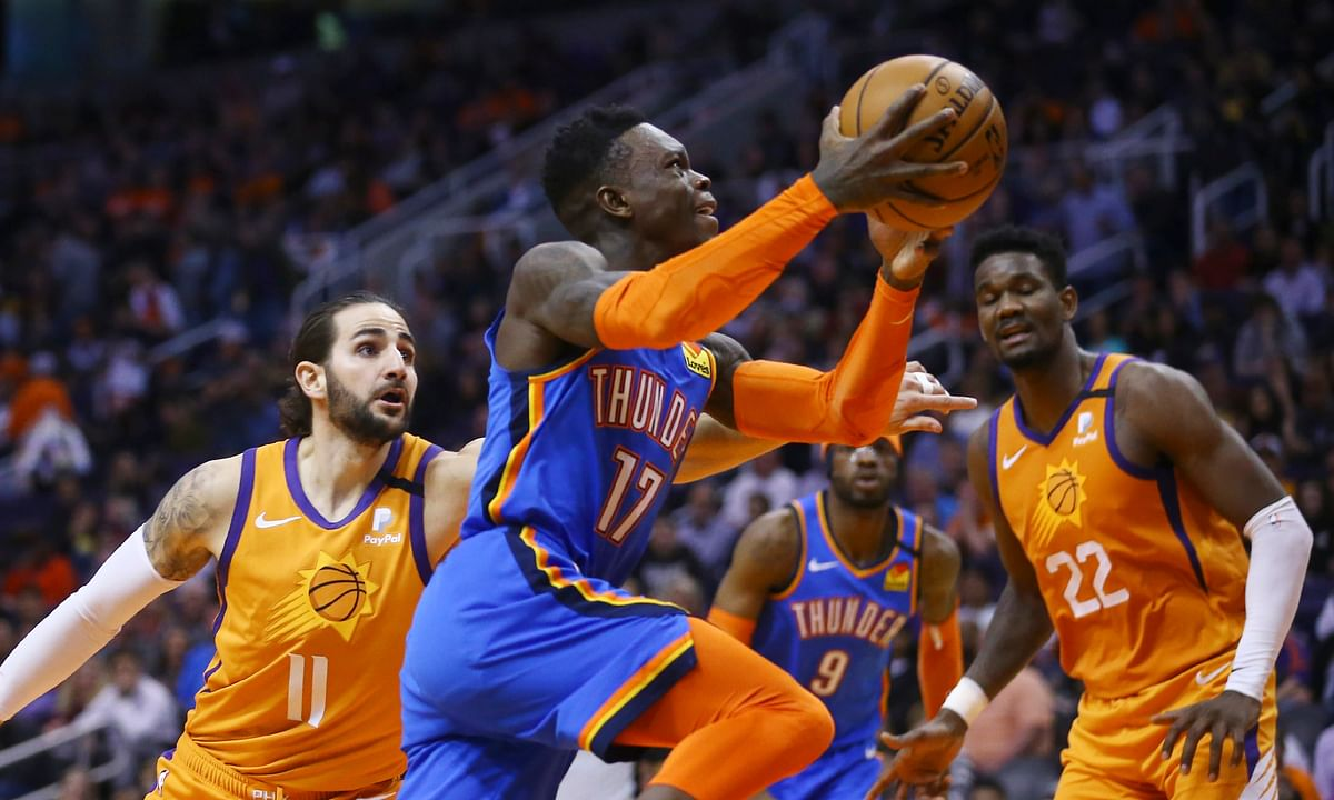 Oklahoma City Thunder guard Dennis Schroder (17) drives past Phoenix Suns guard Ricky Rubio (11) as Suns center Deandre Ayton (22) and Thunder center Nerlens Noel (9) watch during a game in Phoenix on Jan. 31, 2020. Teams may begin making trades Monday and the first deal known to be tentatively agreed upon would send guard Dennis Schröder from Oklahoma City to the champion Los Angeles Lakers for Danny Green and the No. 28 pick in Wednesday's draft.