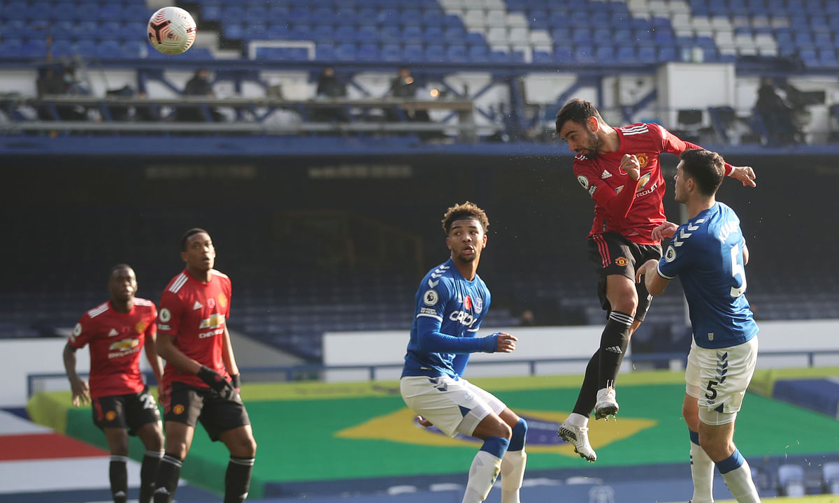 Manchester United's Bruno Fernandes, top, scores his side's opening goal during the English Premier League soccer match between Everton and Manchester United at the Goodison Park stadium in Liverpool, England, Saturday, Nov. 7, 2020.