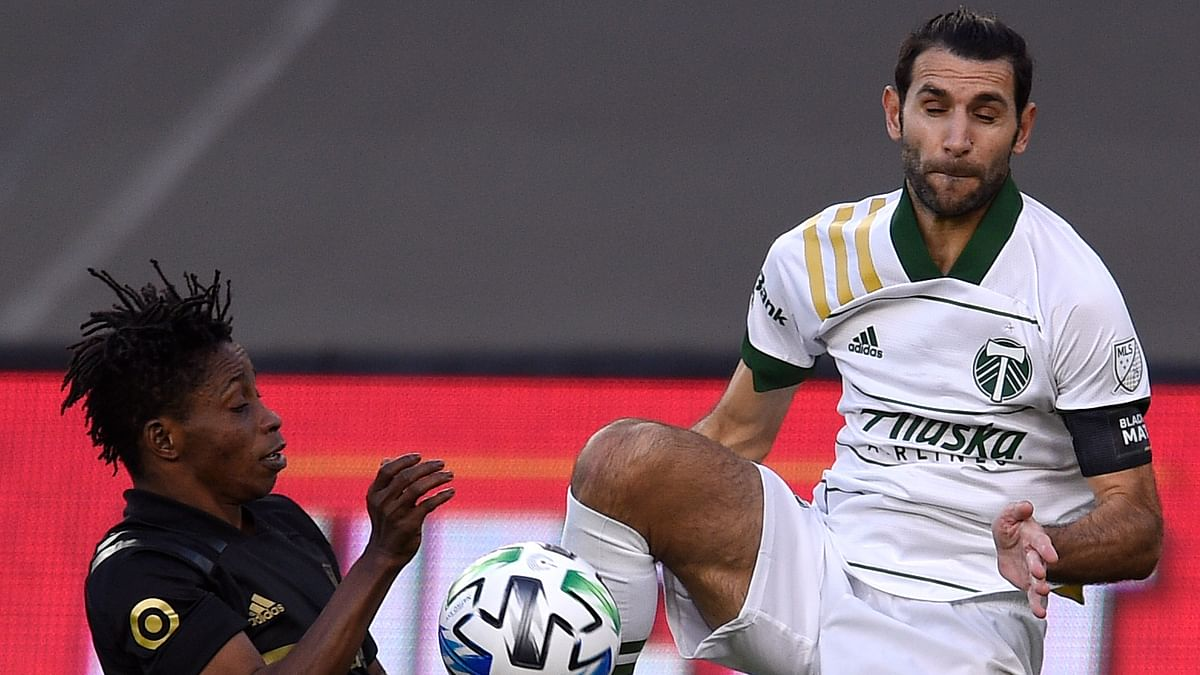 Portland Timbers midfielder Diego Valeri, right, jumps up to battle for the ball with Los Angeles FC midfielder Latif Blessing during the first half of an MLS soccer match in Los Angeles, Sunday, Nov. 8, 2020.