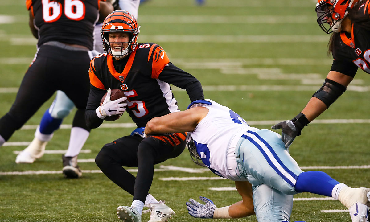 Cincinnati Bengals quarterback Ryan Finley (5) is sacked by Dallas Cowboys defensive tackle Tyrone Crawford (98) in the second half of an NFL football game in Cincinnati, Sunday, Dec. 13, 2020.