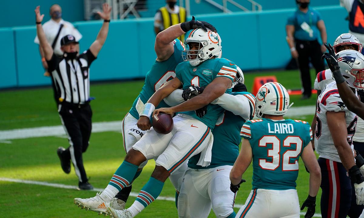 Miami Dolphins quarterback Tua Tagovailoa (1) celebrates his score against the New England Patriots during the second half of an NFL football game Sunday, Dec. 20, 2020, in Tampa, Fla.