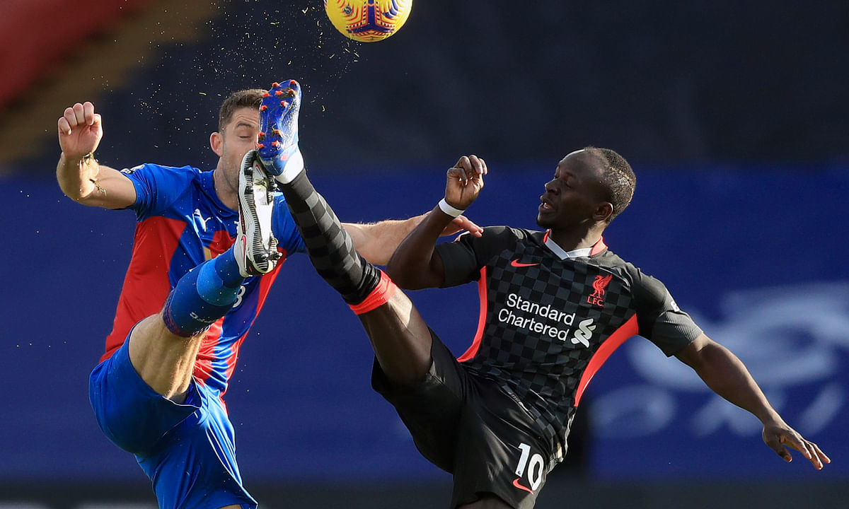 Crystal Palace's Gary Cahill, left, duels for the ball with Liverpool's Sadio Mane during the English Premier League soccer match between Crystal Palace and Liverpool at Selhurst Park stadium in London, Saturday, Dec. 19, 2020.