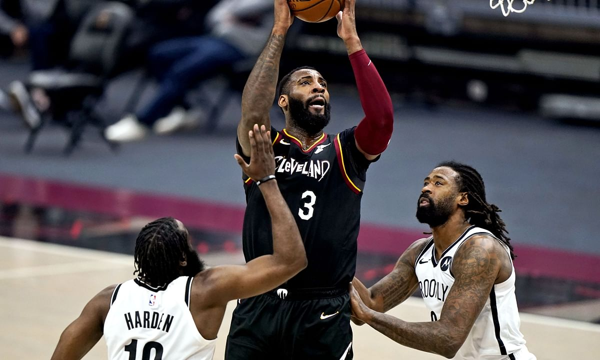 Cleveland Cavaliers' Andre Drummond (3) drives to the basket against Brooklyn Nets' James Harden (13) and DeAndre Jordan (6) during the first half of an NBA basketball game Friday, Jan. 22, 2021, in Cleveland.