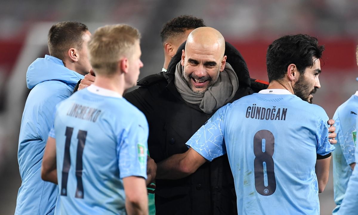 Manchester City's head coach Pep Guardiola, right, congratulates his players after the English League Cup semifinal soccer match between Manchester United and Manchester City at Old Trafford in Manchester, England, Wednesday, Jan. 6, 2021.