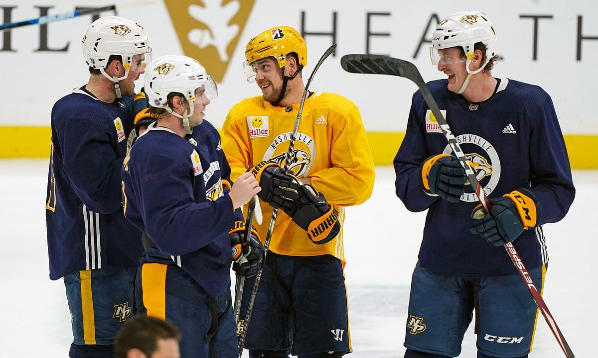 Nashville Predators right wing Viktor Arvidsson, center, talks with teammates during NHL hockey training camp Monday, Jan. 4, 2021, in Nashville, Tenn.