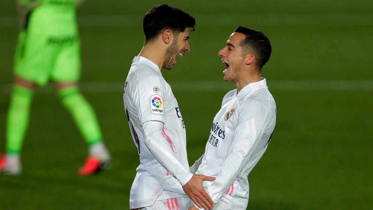 Real Madrid's Marco Asensio, left, celebrates with teammate Lucas Vazquez after scoring his side's second goal during the Spanish La Liga soccer match between Real Madrid and Celta Vigo at the Alfredo Di Stefano stadium in Madrid, Spain, Saturday, Jan. 2, 2021.