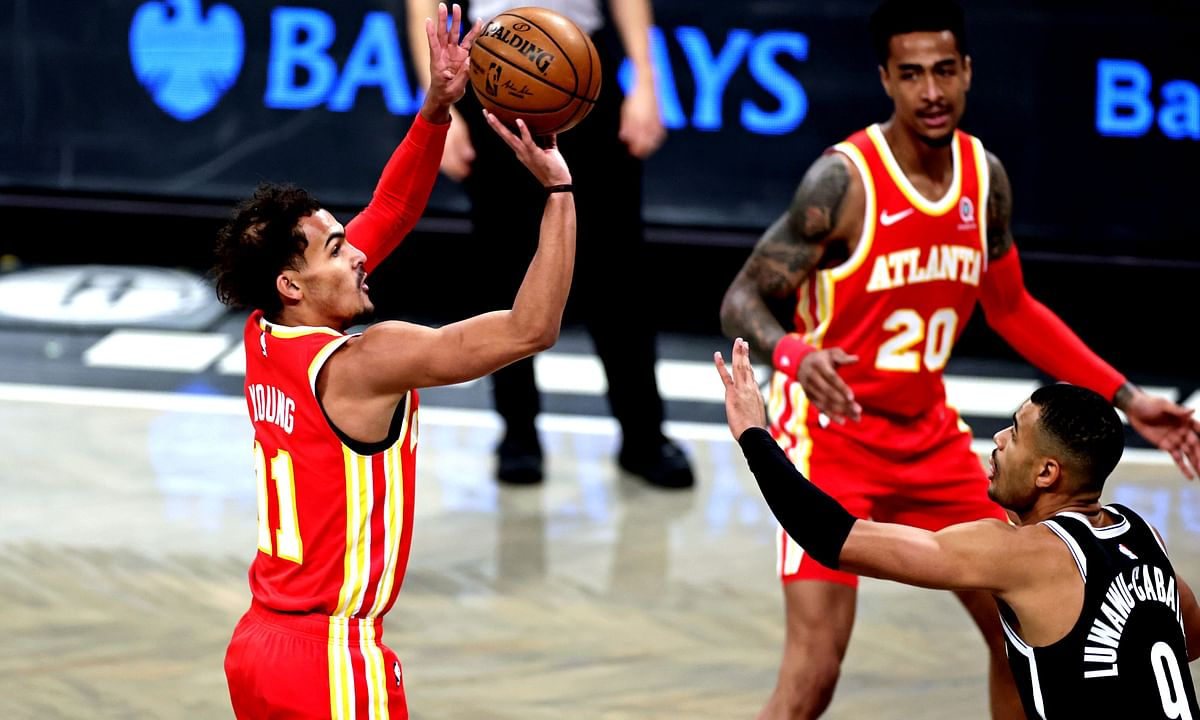Atlanta Hawks guard Trae Young (11) shoots over Brooklyn Nets guard Timothe Luwawu-Cabarrot (9) during the first half of an NBA basketball game Friday, Jan. 1, 2021, in New York.