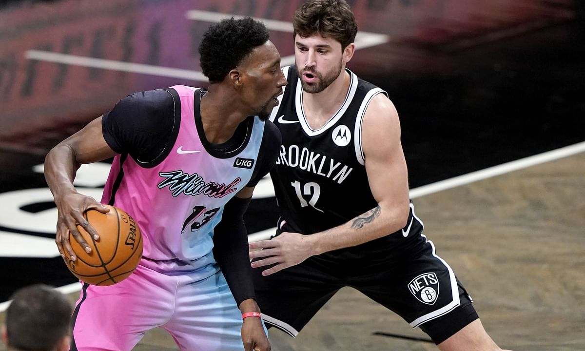 Brooklyn Nets' Joe Harris (12) defends against Miami Heat's Bam Adebayo (13) during the second half of an NBA basketball game Saturday, Jan. 23, 2021, in New York.