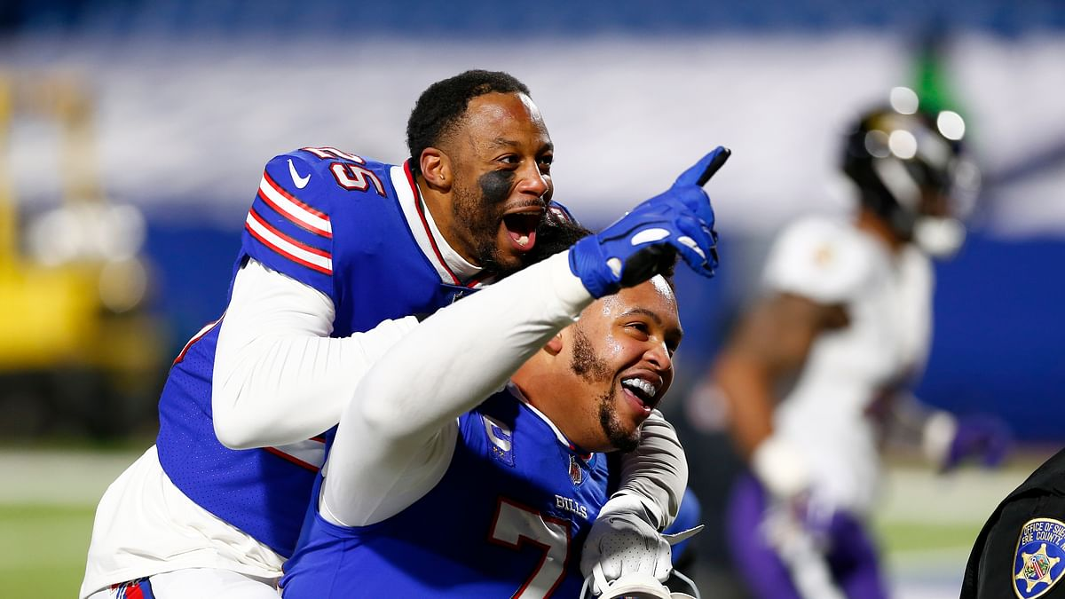 Buffalo Bills' Taiwan Jones (25) celebrates with Dion Dawkins (73) after an NFL divisional round football game against the Baltimore Ravens Saturday, Jan. 16, 2021, in Orchard Park, N.Y. The Bills won 17-3.