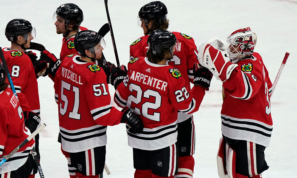 Chicago Blackhawks goalie Kevin Lankinen, right, celebrates with teammates after the team's 4-1 win over the Detroit Red Wings in an NHL hockey game in Chicago, Friday, Jan. 22, 2021.