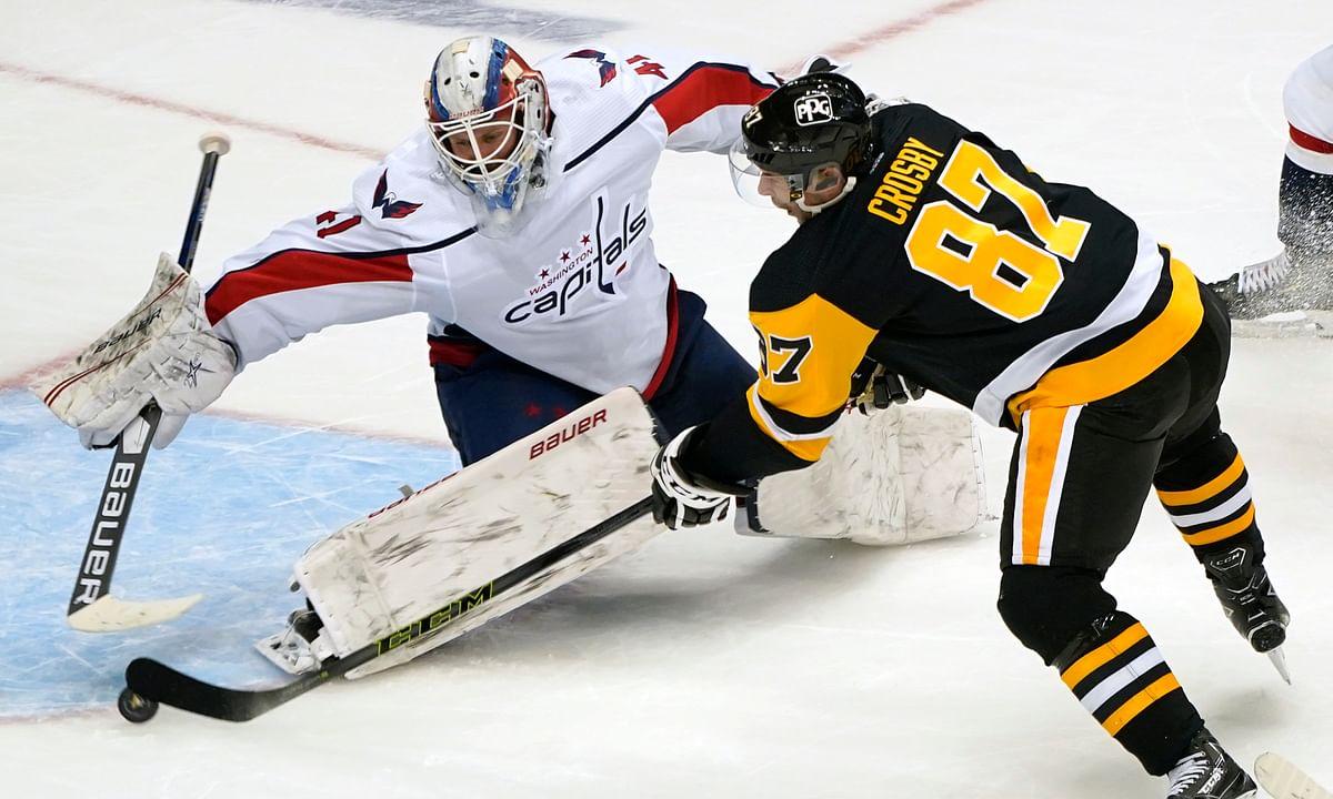 Pittsburgh Penguins' Sidney Crosby (87) gets a shot past Washington Capitals goaltender Vitek Vanecek (41) for an overtime goal in an NHL hockey game in Pittsburgh, Tuesday, Jan. 19, 2021. The Penguins won 5-4.