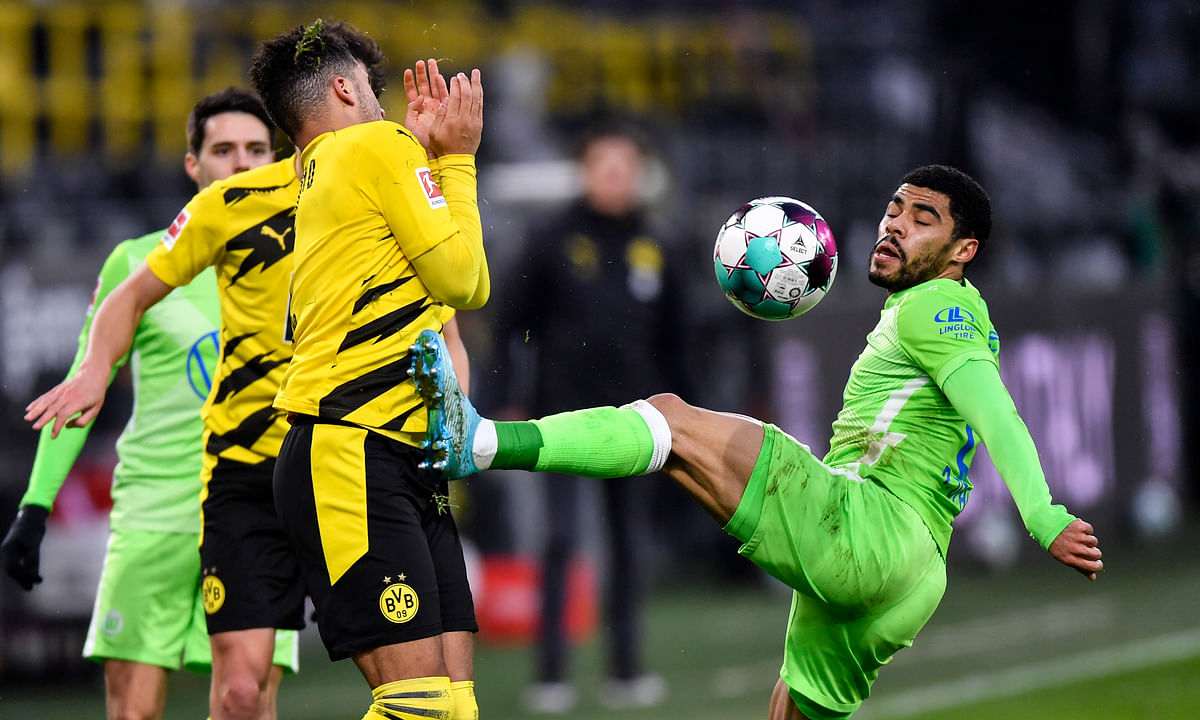 Wolfsburg's Paulo Otavio, right, and Dortmund's Jadon Sancho, left, challenge for the ball during the German Bundesliga soccer match between Borussia Dortmund and VfL Wolfsburg in Dortmund, Germany, Sunday, Jan. 3, 2021.