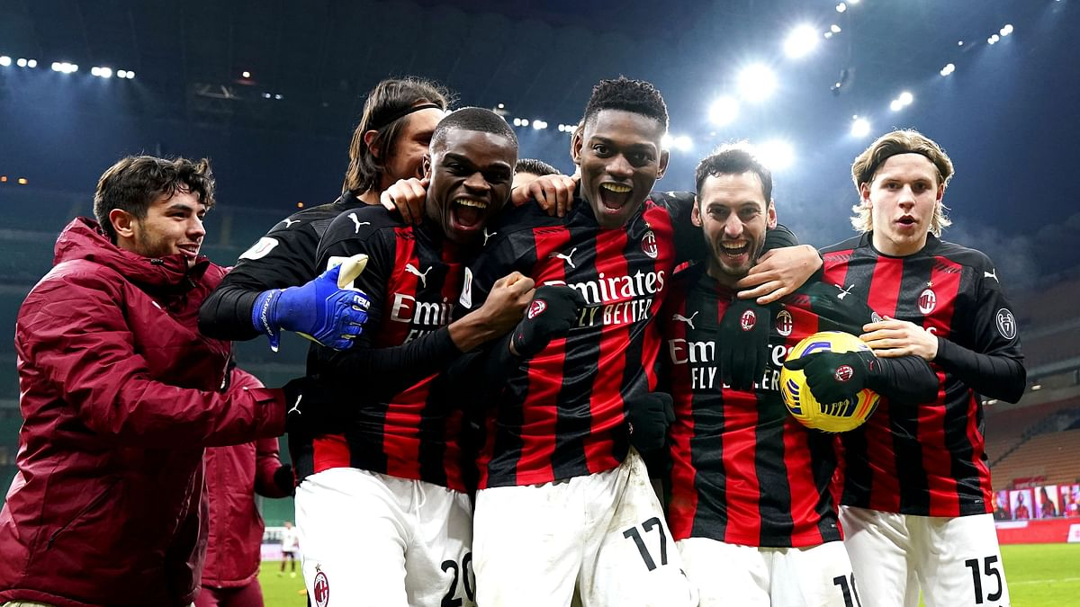 AC Milan team goalkeeper Ciprian Tatarusanu, back, players Kalulu, from second left, Rafael Leao, Hakan Calhanoglu, Diogo Dalot, Brahim Diaz, far left, and Jens Petter Hauge, right, celebrate winning the game at the Italian Cup, round of 16 soccer match between AC Milan and Torino at the San Siro Stadium in Milan Italy, Tuesday, Jan. 12, 2021.
