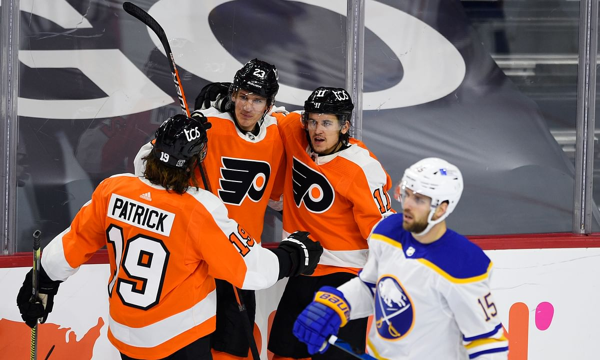 Philadelphia Flyers' Travis Konecny, second from right, celebrates with Oskar Lindblom (23) and Nolan Patrick after Konecny scored a goal past Buffalo Sabres goaltender Carter Hutton during the second period of an NHL hockey game, Tuesday, Jan. 19, 2021, in Philadelphia.