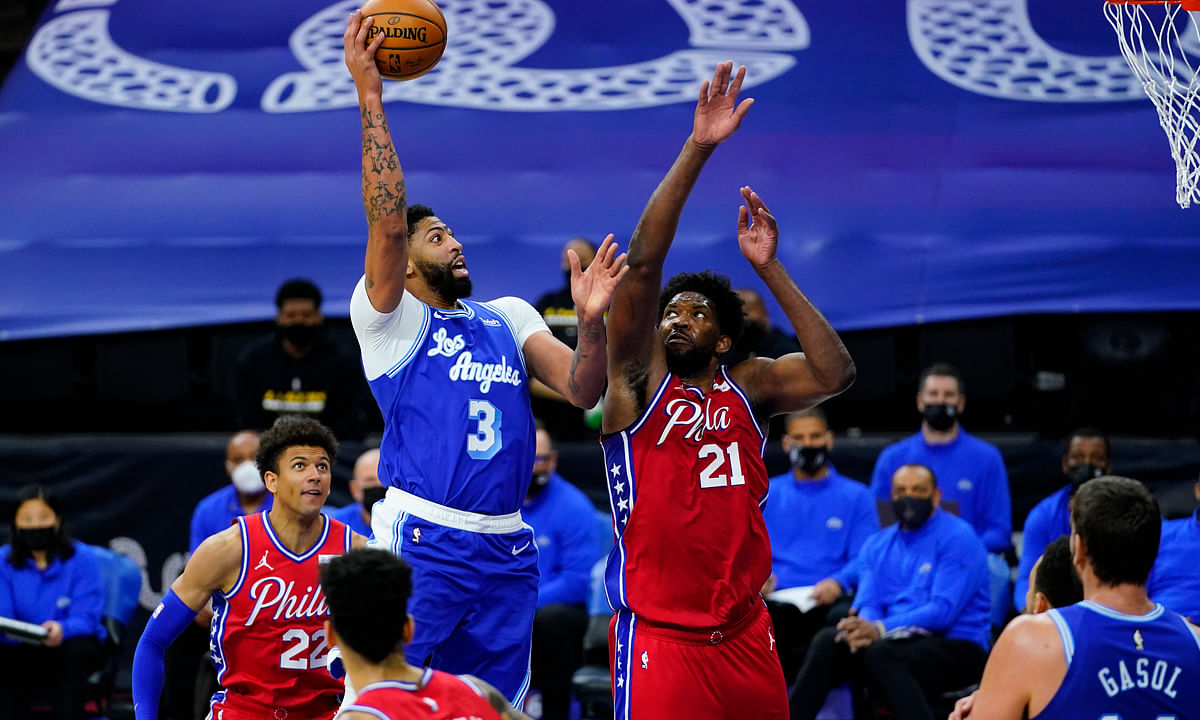 Los Angeles Lakers' Anthony Davis (3) goes up for a shot against Philadelphia 76ers' Joel Embiid (21) during the first half of an NBA basketball game, Wednesday, Jan. 27, 2021, in Philadelphia.
