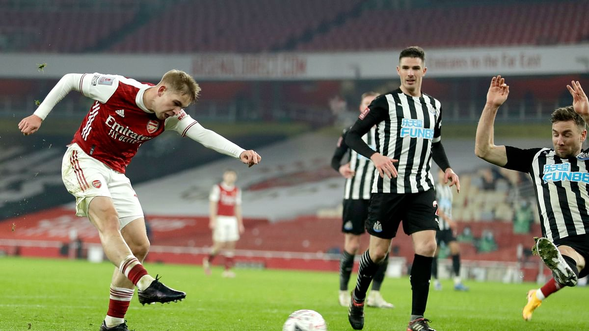 Arsenal's Emile Smith Rowe, left, scores the opening goal during the English FA Cup third round soccer match between Arsenal and Newcastle United at the Emirates Stadium in London, England, Saturday, Jan. 9, 2020.