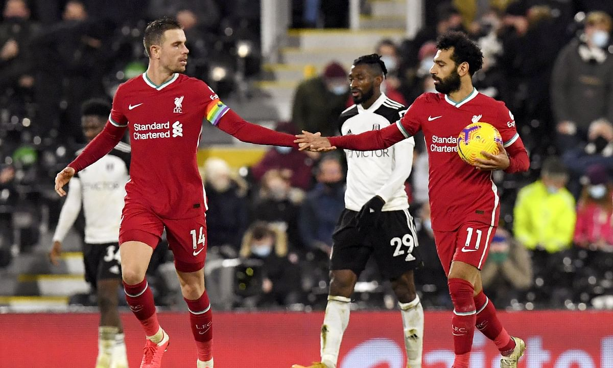 Liverpool's Jordan Henderson congratulates teammate Mohamed Salah after he scored a penalty during the English Premier League soccer match between Fulham and Liverpool, at Craven Cottage stadium, London, Sunday, Dec. 13, 2020.