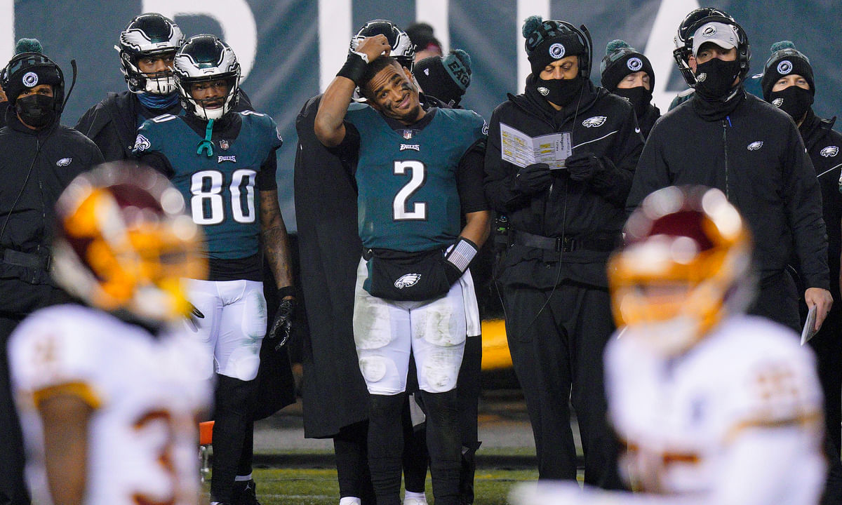 Philadelphia Eagles' Jalen Hurts scratches his head on the sideline during the second half of an NFL football game against the Washington Football Team, Sunday, Jan. 3, 2021, in Philadelphia.