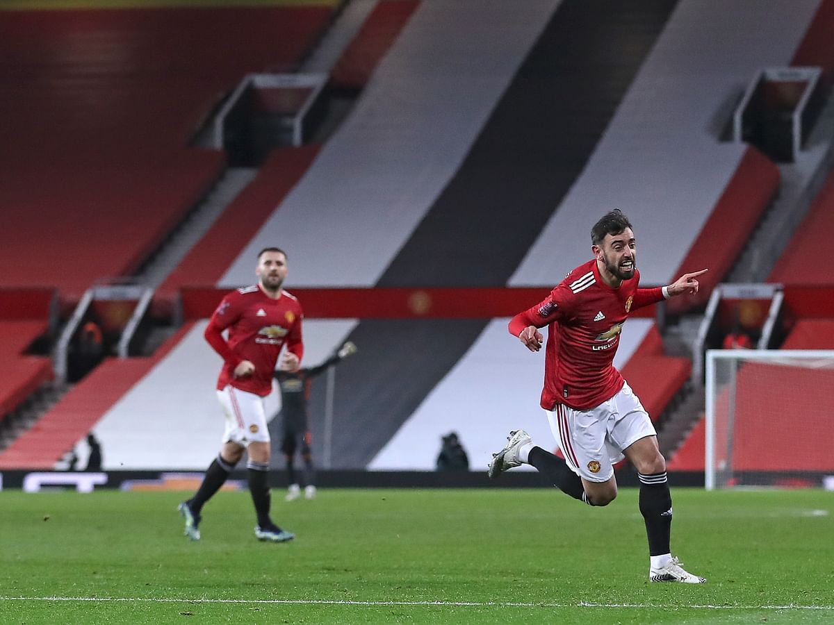 Manchester United's Bruno Fernandes, right, celebrates scoring his side's third goal during the English FA Cup 4th round soccer match between Manchester United and Liverpool at Old Trafford in Manchester, England, Sunday, Jan. 24, 2021.