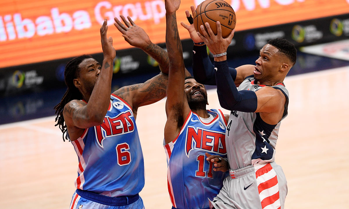 Washington Wizards guard Russell Westbrook, right, goes to the basket against Brooklyn Nets guard Kyrie Irving (11) and center DeAndre Jordan (6) during the first half of an NBA basketball game, Sunday, Jan. 31, 2021, in Washington.