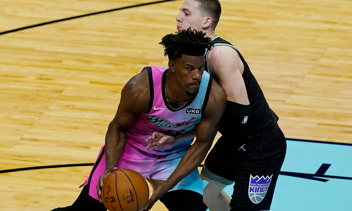 Sacramento Kings guard Kyle Guy (7) defends Miami Heat forward Jimmy Butler (22) during the second half of an NBA basketball game, Saturday, Jan. 30, 2021, in Miami.