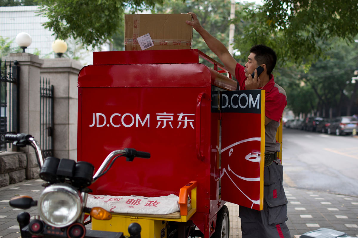 A JD.com employee unloads boxes from a motorcycle in the financial district of Beijing, China. (Photographer Brent Lewin/Bloomberg)