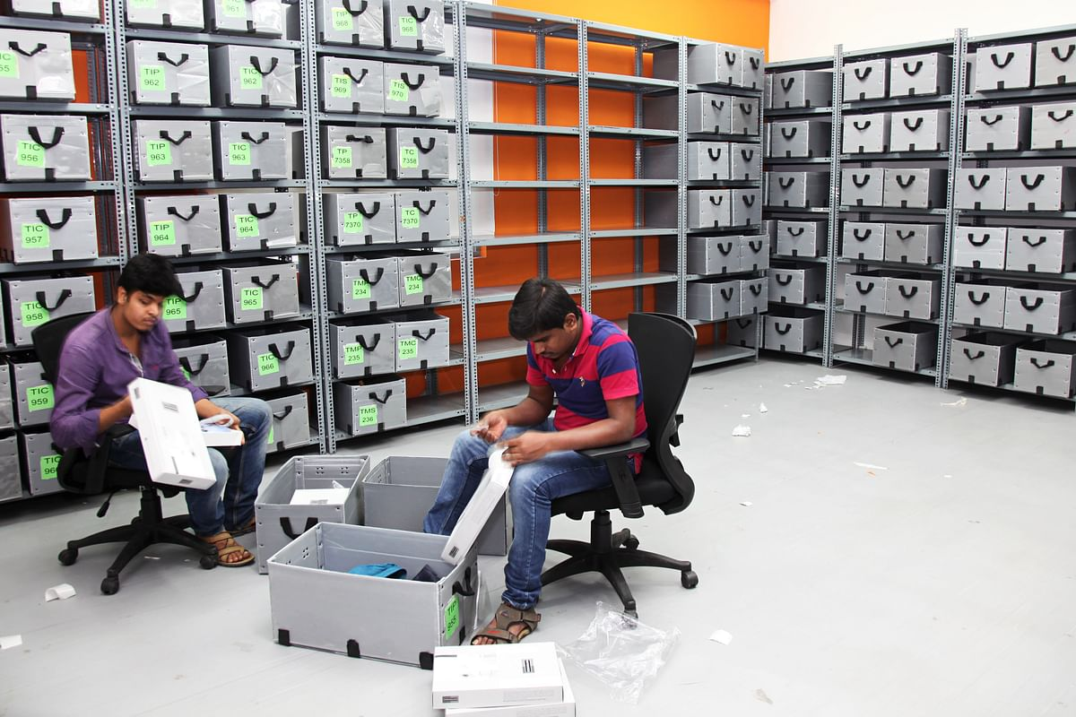 Employees arrange clothing into boxes in the office of Myntra.com, a unit of Flipkart Internet Services Pvt., in Bangaluru. (Photographer: Namas Bhojani/Bloomberg)