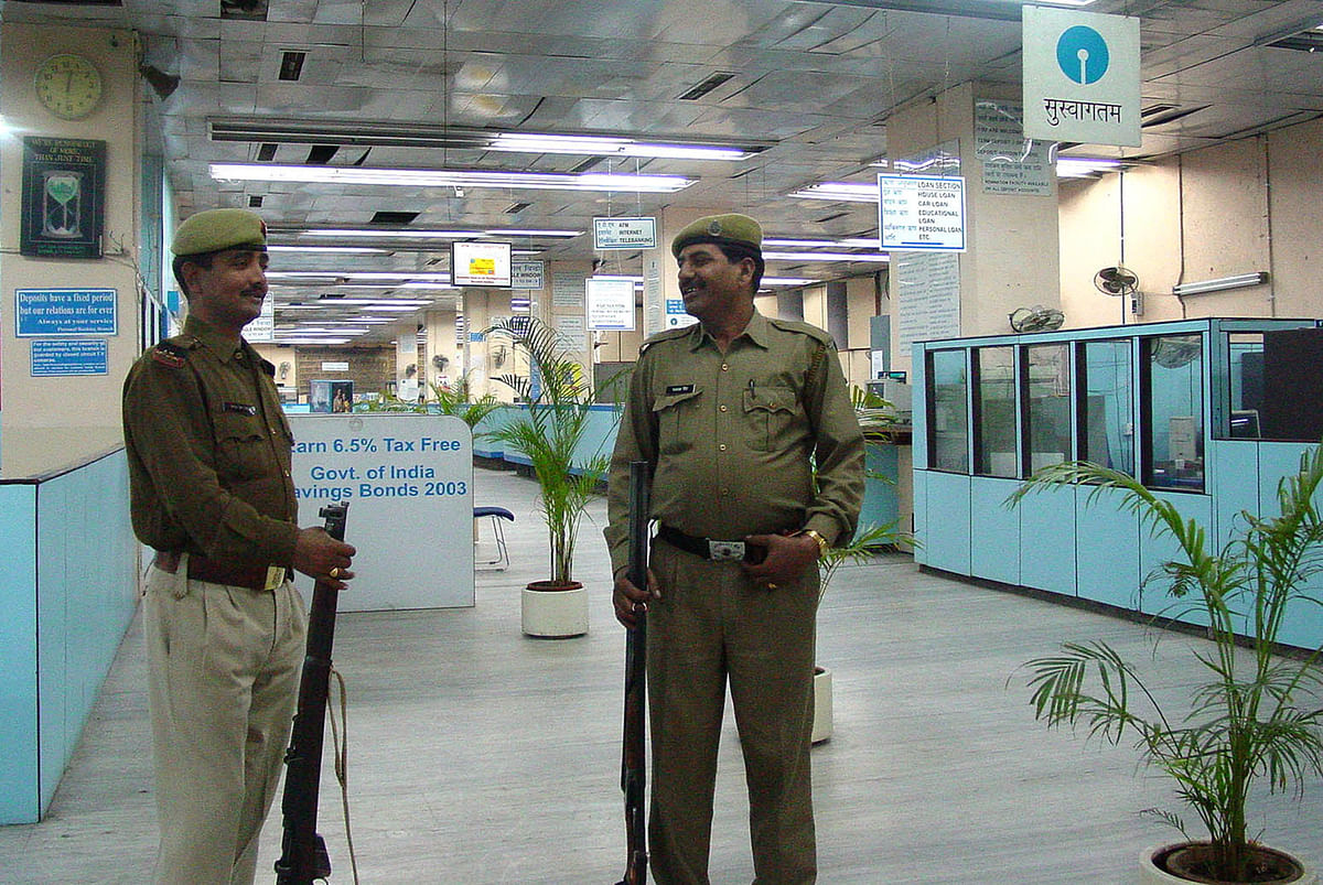 Policemen guard the banking hall of a State Bank of India branch in New Delhi. (Photographer: Sondeep Shankar/Bloomberg News)