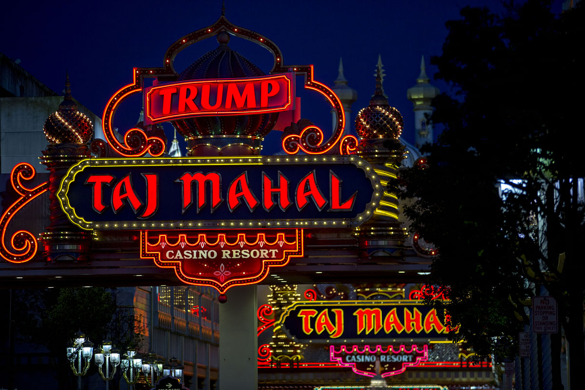 Signage stands outside the Trump Taj Mahal casino and hotel, owned by Trump Entertainment Resorts Inc. (Photographer: Andrew Harrer/Bloomberg)