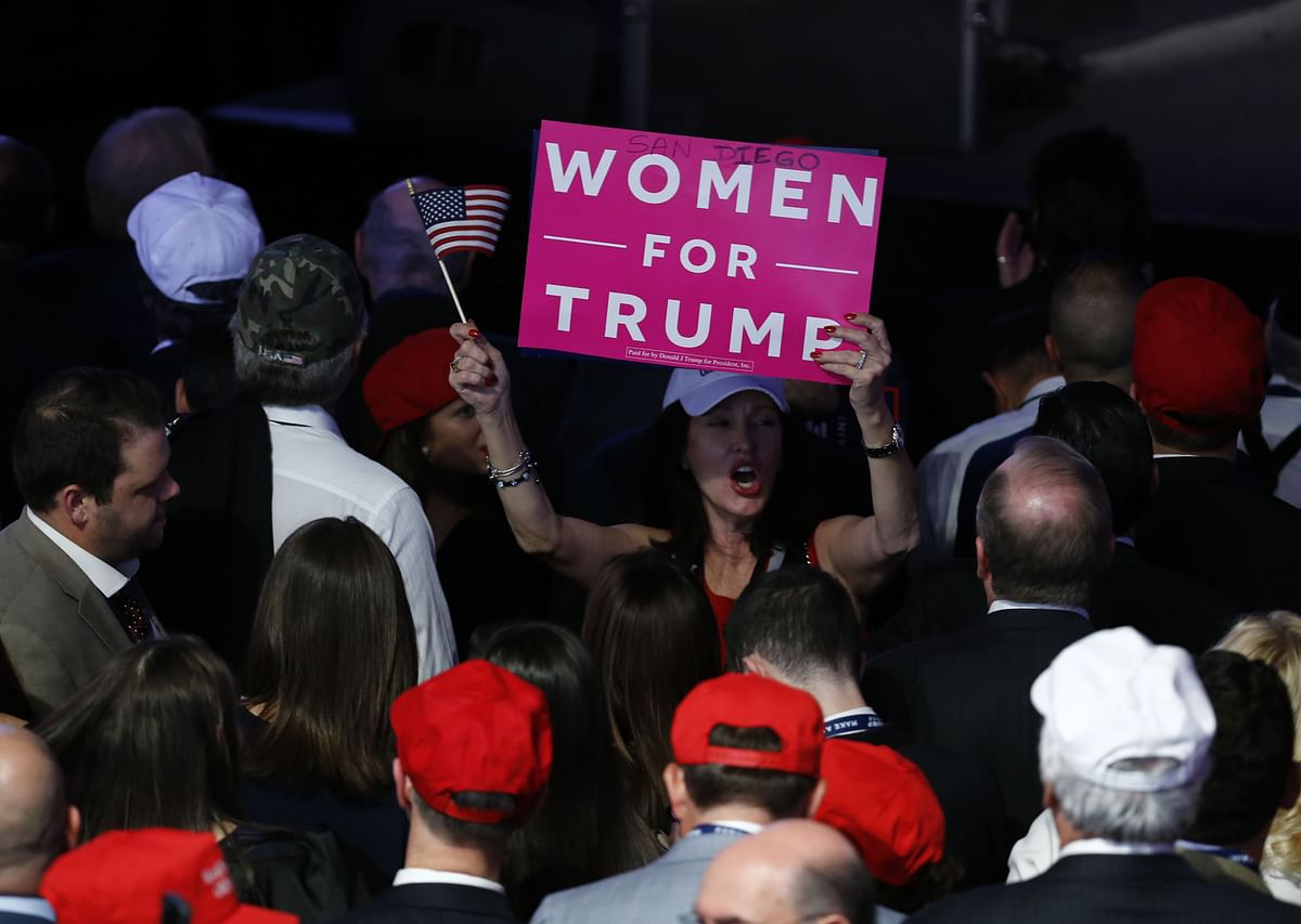 """An attendee holds a """"Women For Trump"""" sign during an election night party for U.S. President-elect Donald Trump at the Hilton Midtown hotel in New York, U.S. (Photographer: Andrew Harrer/Bloomberg)"""